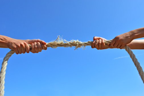 Teenagers hands playing tug-of-war with used rope